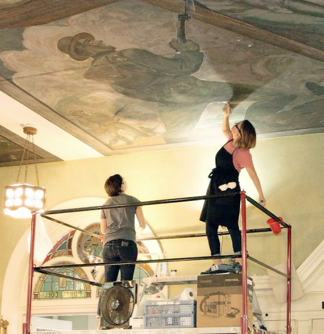 Conservator working on mural ceiling